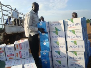 Diocese of Northern Uganda team off-loading water and biscuits for evacuees